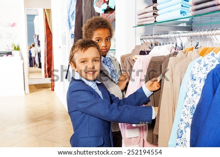 Two boys search clothes while shopping - stock photo