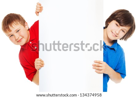 Two boys showing blank white board for advertising to be inserted - stock photo