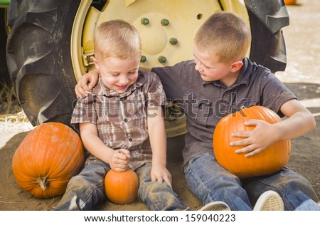Two Boys Sitting Against a Tractor Tire Holding Pumpkins and Talking in Rustic Setting.