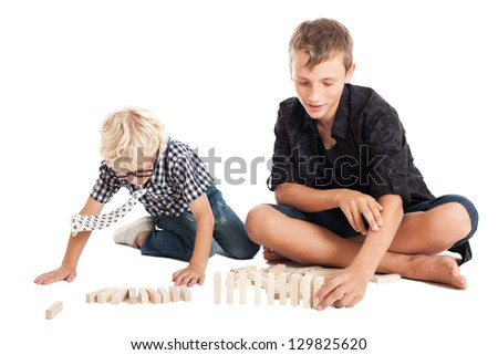 Two boys sitting and playing on the floor. Two brothers, cute kids. Studio shot, isolated on white background. - stock photo