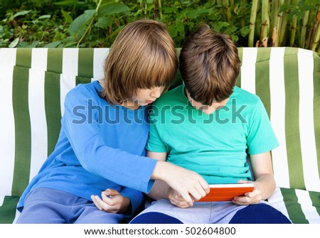 Two Boys Sitting in the Garden Playing with Tablet