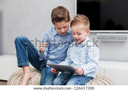 Two boys sitting  in the living room using a tablet pc - stock photo