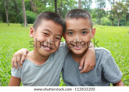 Two boys sitting in the park.