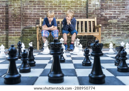 Two boys, sitting on a wooden bench, concentratedly thinking about their next move during an outdoors chess game with life sized pieces. - stock photo