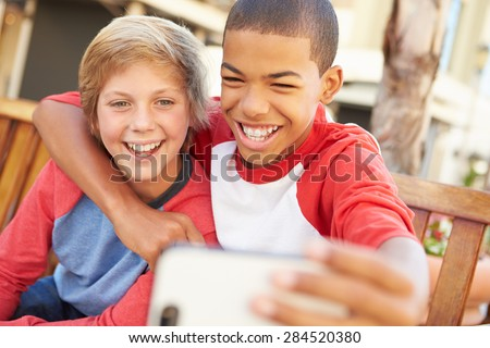 Two Boys Sitting On Bench In Mall Taking Selfie - stock photo