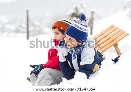 two boys sledding down - stock photo
