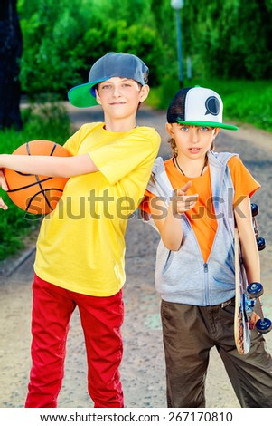 Two boys spend time with skateboard and basketball in the park. Active lifestyle. Summer. - stock photo