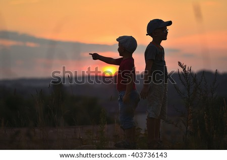 two boys stand at sunset. two boys stand back to back at sunset.  Boys in caps, t-shirts and shorts standing in the grass at sunset