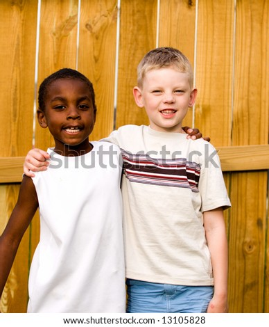 Two boys stand outside with arms around each other