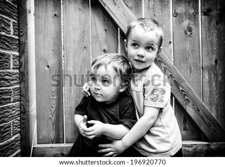 Two boys stand together hugging looking up.  Processed in black and white.  - stock photo
