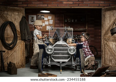 Two boys standing at the mechanic with tools retro car near the garage - stock photo