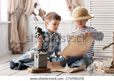 Two boys study found an old map in a bottle - stock photo