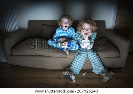 two boys surprised expressions watching television together - stock photo