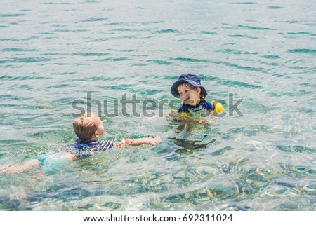 Two boys swimming in the tropical sea