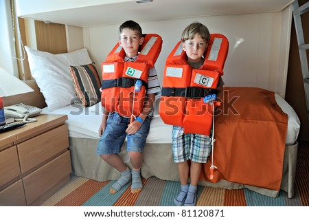 two boys testing their orange life jackets in the cabin of a line cruiser - stock photo