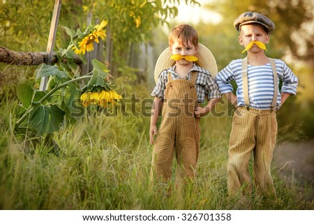 Two boys try on his mustache, made from the petals of a sunflower - stock photo