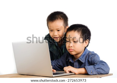 Two boys using and sharing notebook on wood desk