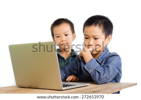 Two boys using and sharing notebook on wood desk look serious
