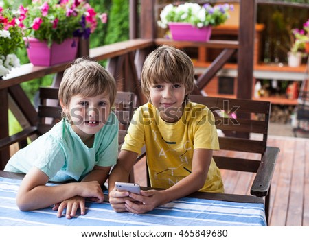 Two boys using mobile phone on terrace in summer day