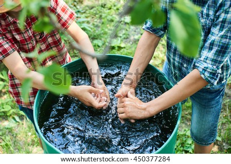 Two boys wash their hands in a barrel of water