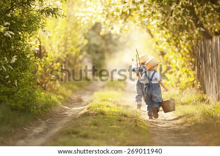 Two boys with fishing rods go on a fishing trip on the narrow rural road in sunny summer day - stock photo