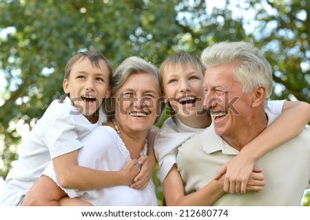 Two boys with grandparents over summer natural background - stock photo