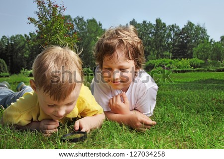 two boys with magnifying glass outdoors - stock photo