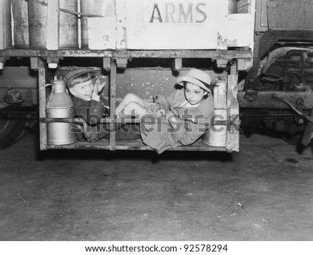 Two boys with milk canisters in a cargo bay of a truck - stock photo