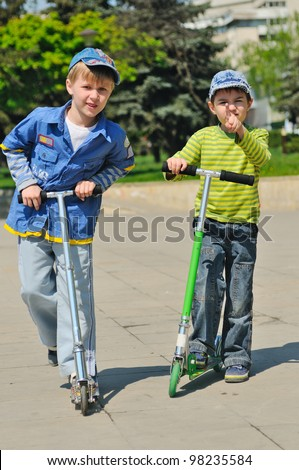 Two boys  with scooters - stock photo