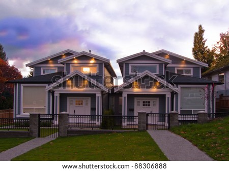 Two brand new houses at sunrise-sunset with lights on