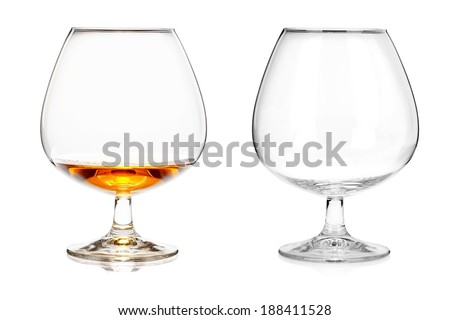 Two brandy glasses (empty and with alcohol) isolated on white background - stock photo