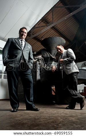 two brave businessmen stand excited next to their factory machine