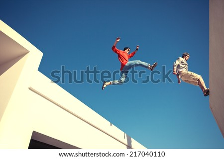 two brave men jumping over the roof, and little motion blur - stock photo