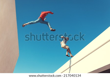 two brave men jumping over the roof, and little motion blur