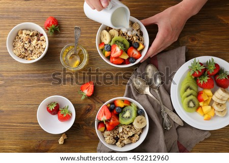 two breakfast bowl with fruits, hand pouring milk