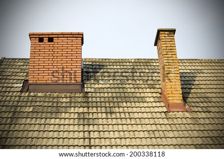 two brick chimneys on the roof - stock photo