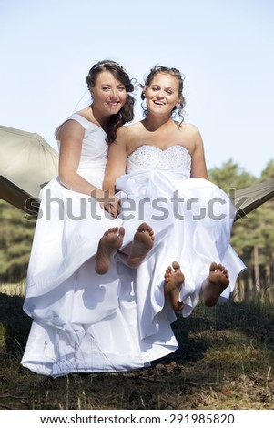 two brides show bare feet in hammock against blue sky with forest background - stock photo