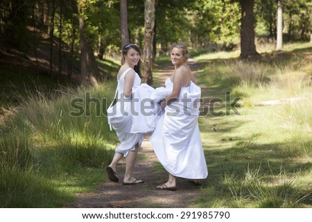 two brides walk on forest path with skirts in their arms while looking back smiling - stock photo