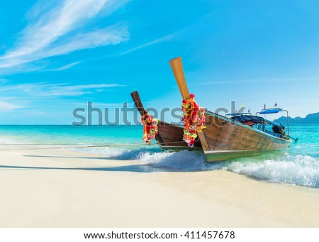 Two bright decorated thai longtail boats at Long Beach (Had Yao beach), best Phi Phi Don island beach, Thailand, view to Phi Phi Lee island silhouette at horizon - stock photo