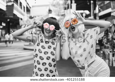Two bright funny cool fashionable girl in blue and pink wigs. In the hands holding the sweet donuts. Black-and-white photography with a color separation of a donut. - stock photo