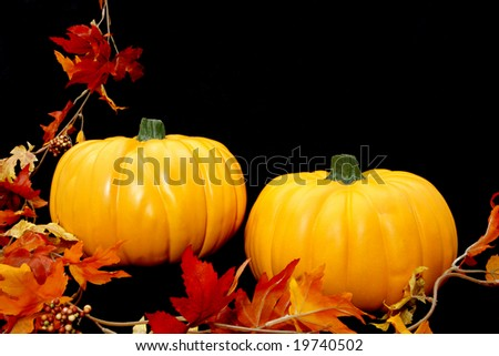 Two bright orange pumpkins arranged against a black background with some fall leaves to the left.