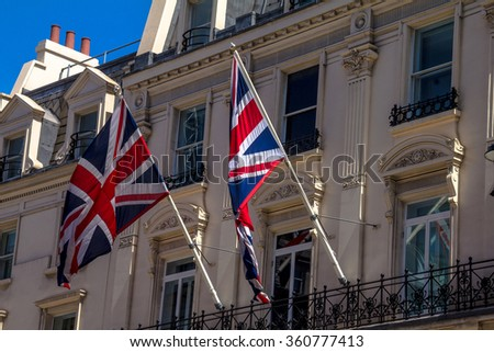 Two British flag flying on the balcony of a historic building in central London