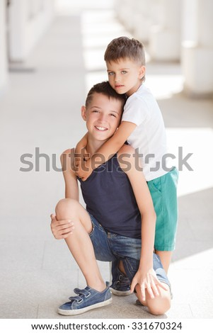 Two brother hugging each other outdoor, smiling and laughing. Two young male friends playing outdoors smiling. - stock photo