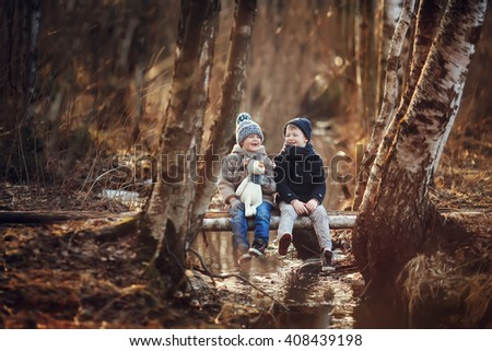 Two brother in a coat and hat sitting on a bridge with a toy dog fun talking and laughing in the spring park - stock photo