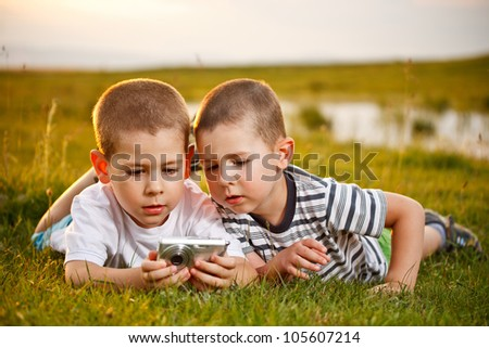 Two brother lying on meadow and taking pic on their camera - stock photo