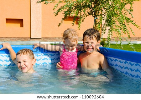 Two brothers and baby sister swimming in the pool