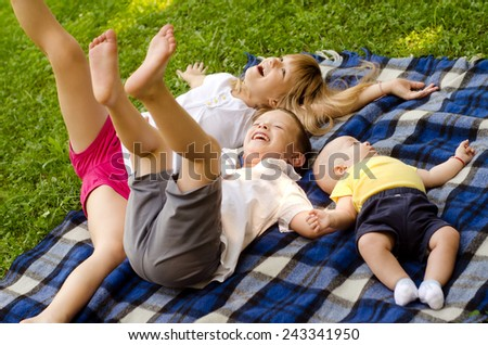 Two brothers and sister having fun on the meadow on sunny summer day. - stock photo