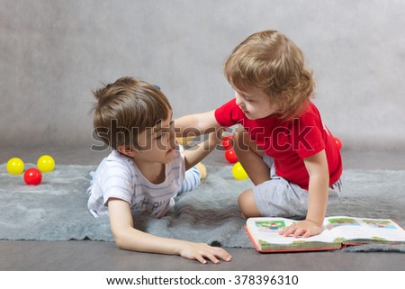 Two brothers 6 and 3 years old are reading the book on a gray background