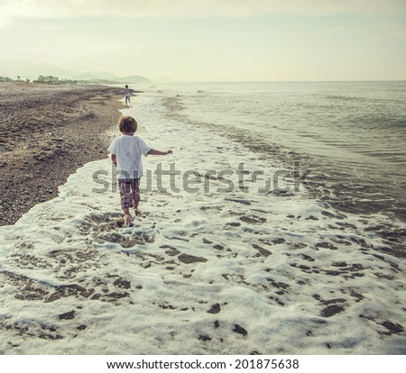 Two brothers are running on beach, outdoor - stock photo