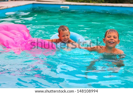 Two brothers are swimming in the pool - stock photo